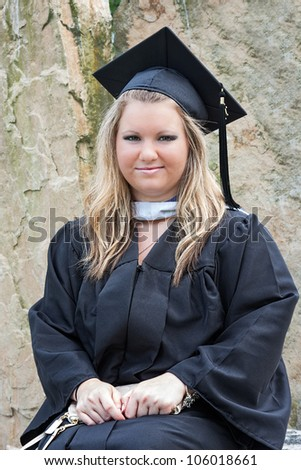 Portrait of a female college graduate student. She is wearing a graduation cap and gown on graduation day. - stock photo