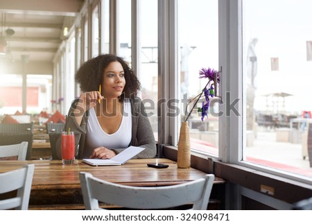 Portrait of a female college student sitting at cafe looking out of window daydreaming - stock photo