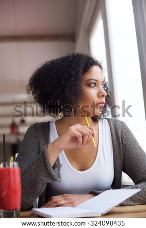 Portrait of a female college student with pencil and paper daydreaming - stock photo