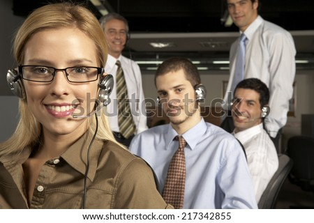 Portrait of a female customer service representative smiling with her four colleagues behind her - stock photo
