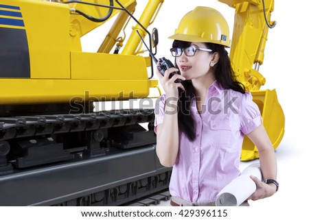 Portrait of a female developer talking on the walkie talkie with an excavator background, isolated on white background - stock photo