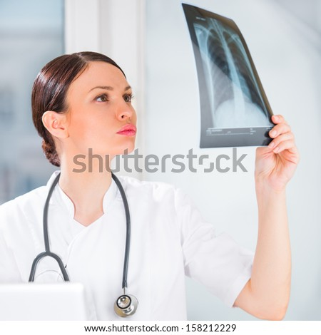 Portrait of a female doctor holding chest xray results and using her laptop computer at clinic - stock photo