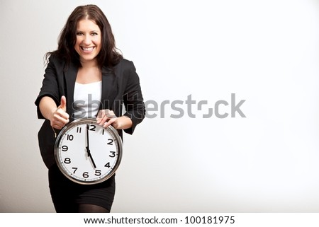 Portrait of a female employee giving a thumbs up sign while holding a clock, isolated on gray background - stock photo