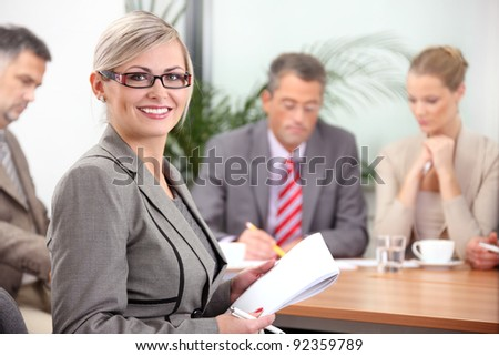 Portrait of a female executive with colleagues in the background - stock photo