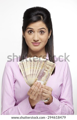 Portrait of a female executive with currency