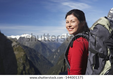 Portrait of a female hiker with backpack against mountain peaks - stock photo