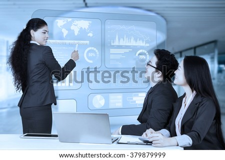 Portrait of a female Indian entrepreneur explaining business solutions with a virtual screen to her partners - stock photo