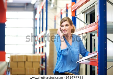 Portrait of a female logistics worker controlling stock and talking on cellphone in warehouse - stock photo