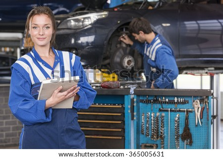 portrait of a female mechanic in a automotive workshop  - stock photo