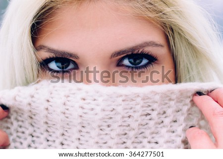 Portrait of a female on winter, focus on eyes. Mouth covered by scarf. - stock photo