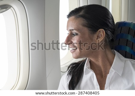 Portrait of a female passenger looking out her airplane window - stock photo