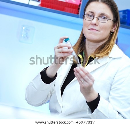 Portrait of a female researcher carrying out experiments in a research lab  (color toned image)