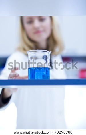 portrait of a female researcher carrying out research in a chemistry/biochemistry lab (color toned image; shallow DOF)