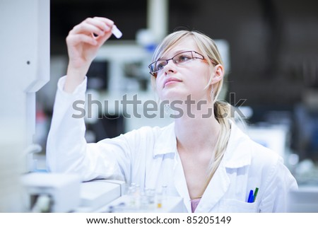 portrait of a female researcher/chemistry student carrying out research in a chemistry lab (color toned image; shallow DOF) - stock photo