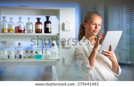 Portrait of a female researcher doing research in a lab, using a tablet computer for data collection and visualization(shallow DOF; color toned image) - stock photo
