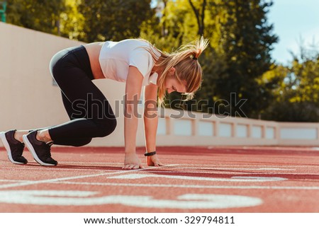 Portrait of a female runner in start position at outdoor stadium
