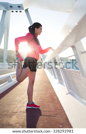 Portrait of a female runner stretching legs muscles before her evening jog in the fresh air in summer, young athletic woman having fitness training outdoors, sporty girl doing physical exercises  - stock photo