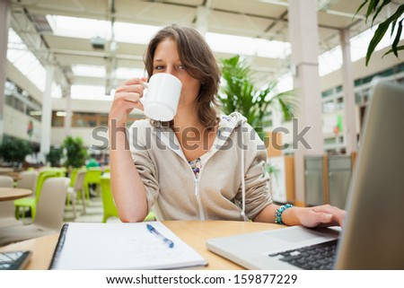 Portrait of a female student drinking coffee while using laptop at cafeteria table - stock photo