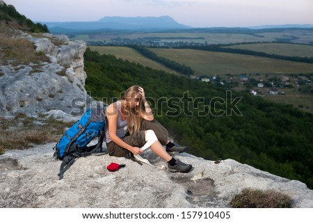 Portrait of a female tourist applying an arm medical bandage in mountains during the journey - stock photo