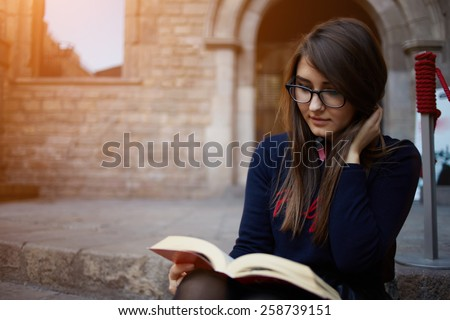 Portrait of a female university student reading interesting book on campus, charming teenager sitting outdoors with open book, attractive young girl read absorbing book, flare light, filtered image - stock photo