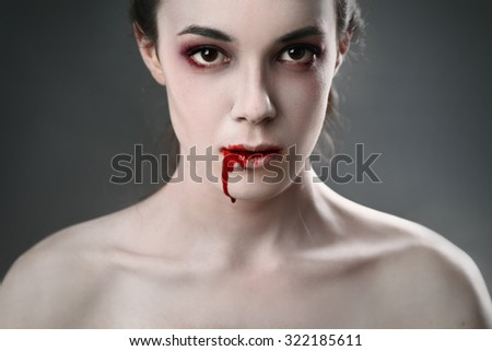 Portrait of a female vampire over black background - stock photo
