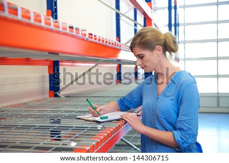 Portrait of a female warehouse employee standing next to shelves and writing on clipboard