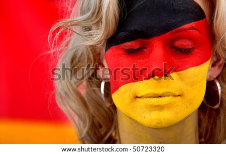 Portrait of a female with a german flag painted on her face - stock photo