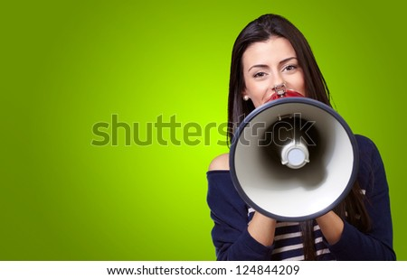 Portrait Of A Female With Megaphone On A Green Background - stock photo