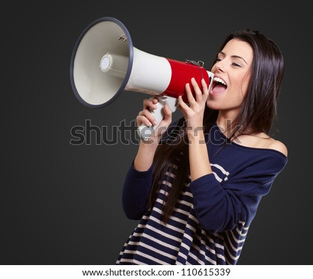 Portrait Of A Female With Megaphone On Black Background - stock photo