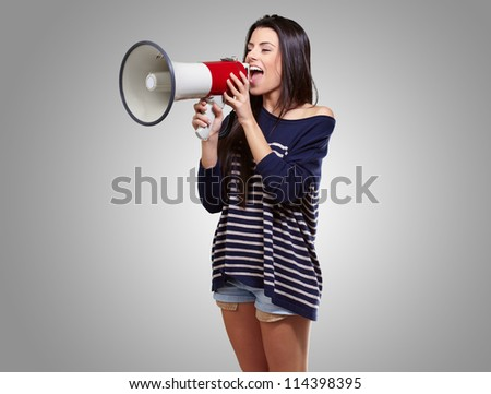 Portrait Of A Female With Megaphone On Gray Background - stock photo