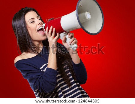 Portrait Of A Female With Megaphone On Red Background - stock photo
