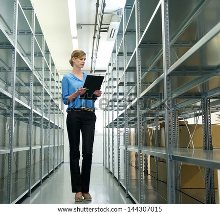 Portrait of a female worker with clipboard, organizing inventory and stock in warehouse - stock photo