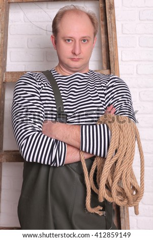 Portrait of a fisherman in waders with rope - stock photo