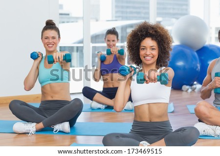 Portrait of a fit class lifting dumbbell weights in a bright gym