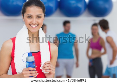 Portrait of a fit female holding water bottle with fitness class in background at gym - stock photo