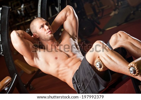 Portrait of a fit lean young man exercising in a gym. - stock photo