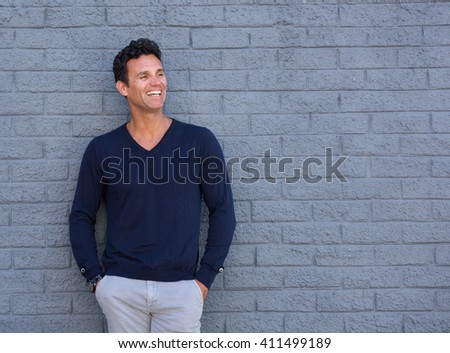 Portrait of a fit older man smiling against gray wall - stock photo
