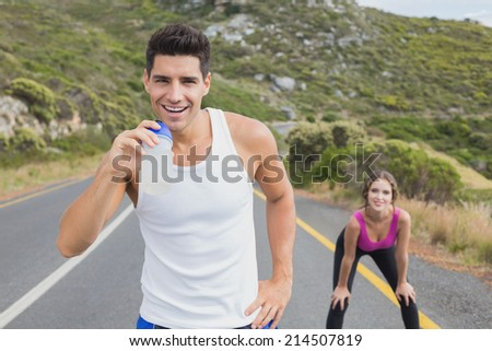 Portrait of a fit young couple standing on the open road together - stock photo