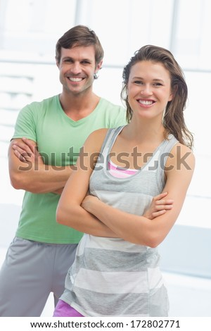 Portrait of a fit young couple standing with arms crossed in bright exercise room - stock photo