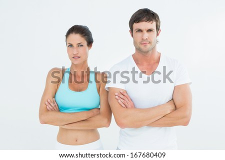 Portrait of a fit young couple with arms crossed standing over white background - stock photo