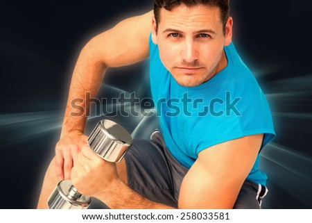Portrait of a fit young man exercising with dumbbell against abstract background - stock photo