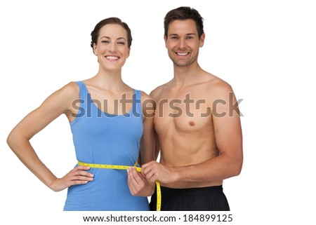 Portrait of a fit young man measuring womans waist over white background - stock photo
