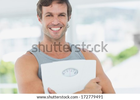 Portrait of a fit young man standing with scale in a bright exercise room - stock photo