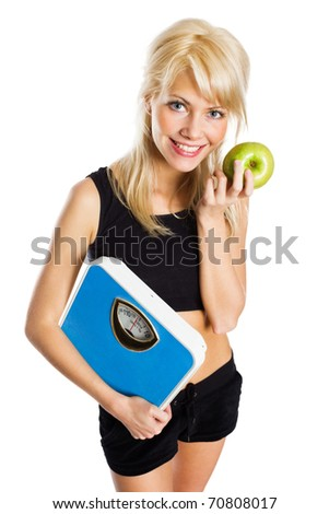 Portrait of a fit young woman holding weight scale and a green apple - stock photo