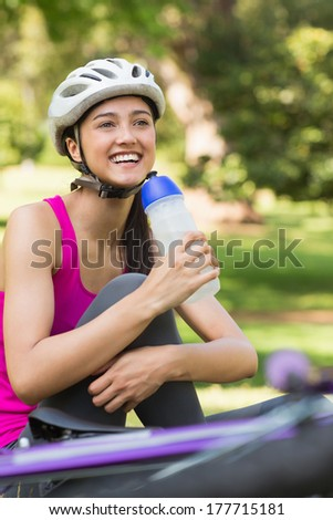 Portrait of a fit young woman in helmet holding water bottle at the park - stock photo