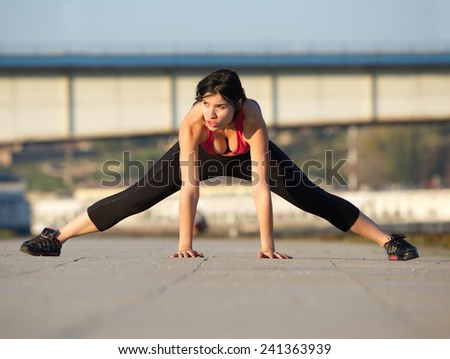 Portrait of a fit young woman stretching muscles outdoors - stock photo