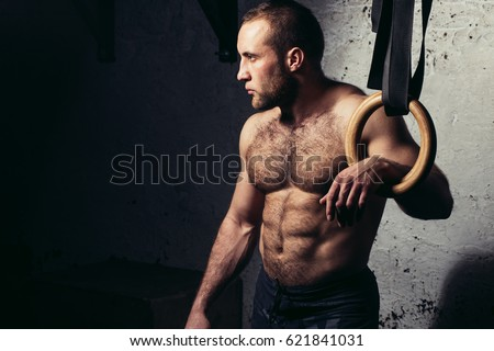 Portrait Of A Fitness Man Training Arms With Gymnastics Rings In The Gym