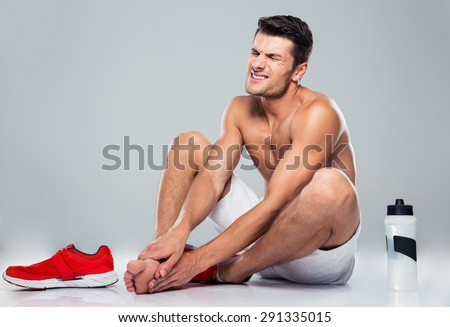Portrait of a fitness man with foot pain over gray background
