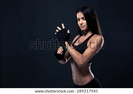 Portrait of a fitness woman standing over black background and looking at camera - stock photo