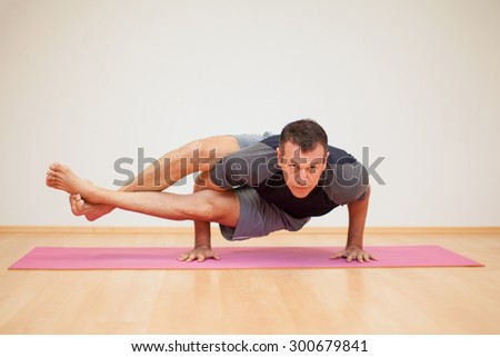 Portrait of a flexible man practicing a few yoga poses in a gym - stock photo